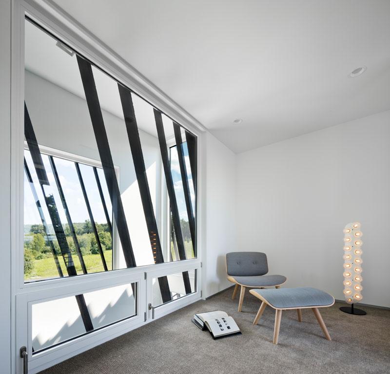 Современная спальня с большим окном использующим сайдинг shou sugi ban